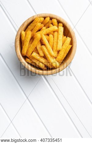 French fries. Salted snack. Potato chips in bowl on white table. Top view.