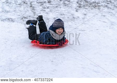 A Little Boy Rides A Sled From A Winter Slide.