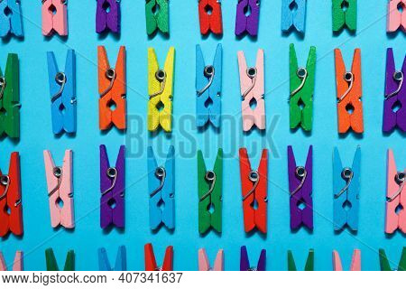 Small clothespins on a blue table.
