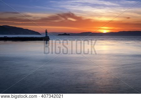 Sunset At Trondheim Harbour In Norway With A Small Lighthouse In The Distance