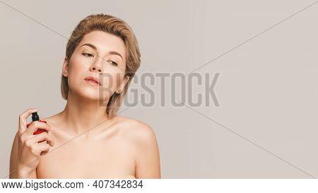 Beautiful Young Blonde Woman Uses Eau De Toilette. Horizontal Studio Shot On Beige Background, Copy