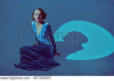 Fashion model in a long elegant dress and with hair and makeup in the style of the 20s posing in the circle of light. Light and shade.