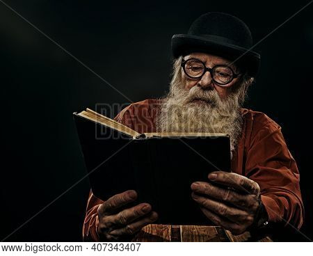 A wise old man with a long gray beard in a bowler hat and glasses is reading an old book. Black background.