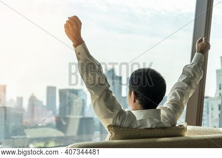 Business Achievement Ambition Concept With Businessman Raising Fists Happily, Relaxing In Office Or