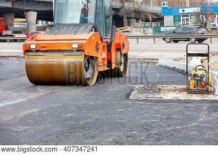 A Heavy Road Vibratory Roller And A Petrol Vibratory Compactor Plate Are Used To Compact Fresh Aspha