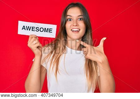 Beautiful caucasian woman holding awesome banner smiling happy pointing with hand and finger