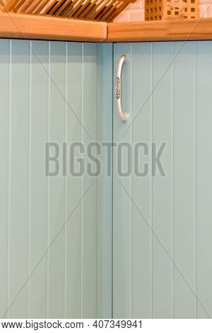 Light Blue Front Of Kitchen Cabinet With Graceful Handles. Part Of Modern Kitchen Interior Close-up.