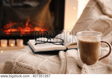 Cup Of Coffee, Book And Glasses Near Fireplace Indoors, Space For Text. Cozy Atmosphere