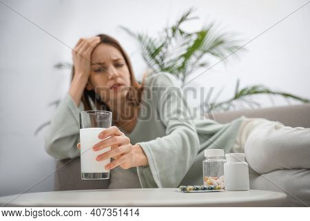 Woman Taking Medicine For Hangover At Home, Focus On Hand