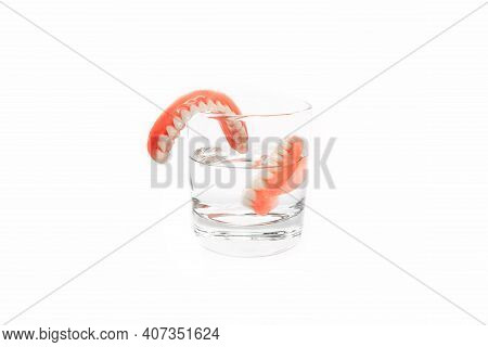 Dental Prosthesis Care. Full Removable Plastic Denture Of The Jaws. A Set Of Dentures In A Glass Of