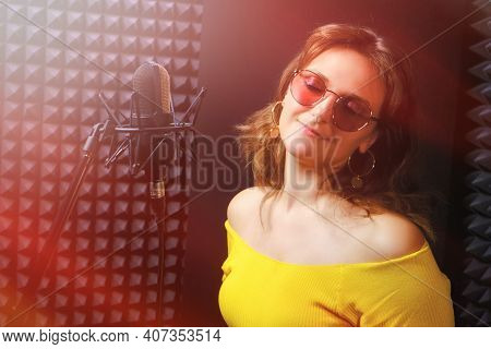 Recording A Song At The Music Studio. Woman In Sunglasses Recording A Song In A Professional Studio.