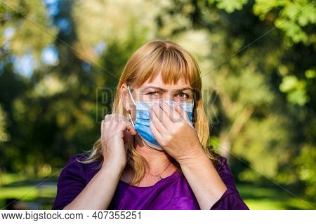 Woman In Medical Mask Shows With Her Hands That The Situation Is Choking Her. Woman Having Difficult