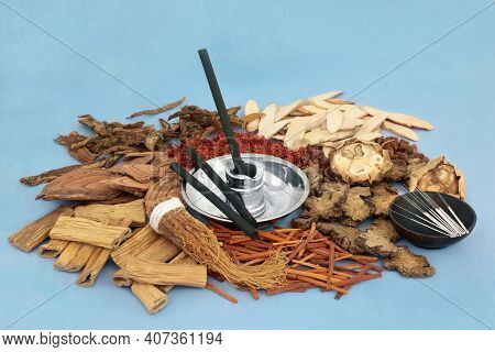 Chinese acupuncture needles and   moxa sticks used in moxibustion treatment with herbs and spice used in traditional herbal medicine. On mottled blue background. Holistic health care concept.