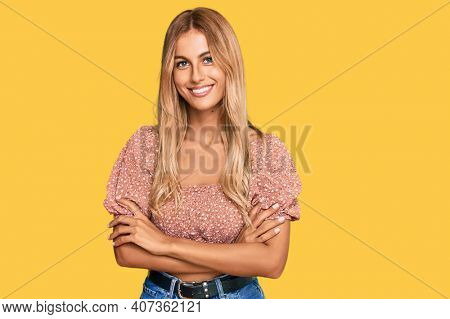 Beautiful blonde young woman wearing summer top happy face smiling with crossed arms looking at the camera. positive person.
