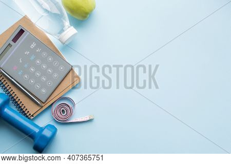 Paper Notebook, Calculator, Pen, Bottle Of Water, Dunbbell, Measuring Tape And Apple On Blue Backgro