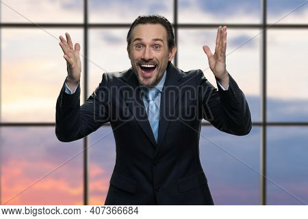 Portrait Of Mature Excited Businessman Is Celebrating. Happy Excited Boss Raising Hands Up And Rejoi