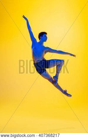 Freedom. Young And Graceful Ballet Dancer On Yellow Studio Background In Neon Light. Art, Motion, Ac