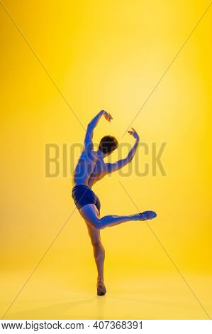 Strong. Young And Graceful Ballet Dancer On Yellow Studio Background In Neon Light. Art, Motion, Act