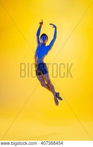 Inspiration. Young And Graceful Ballet Dancer On Yellow Studio Background In Neon Light. Art, Motion