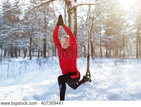 Outdoor Winter Fitness Concept. Sporty Senior Man Training With Resistance Straps At Snowy Forest. F