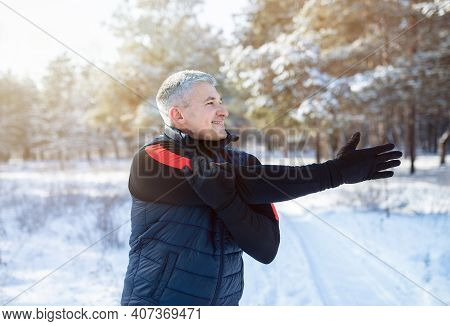 Winter Outdoor Workout Concept. Cheerful Mature Guy Doing Warmup Exercises Before His Run In Snowy W