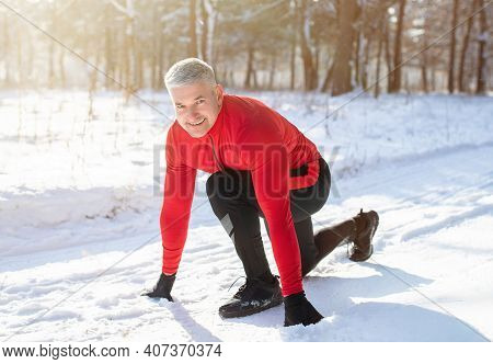 Athletic Senior Man Ready To Run During Winter Training Outside In Cold Snowy Weather. Happy Mature
