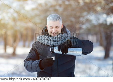 Happy Senior Man In Warm Jacket And Scarf Pouring Tea From Thermos Flask In Snowy Winter Park. Posit