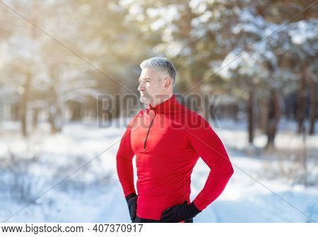 Athletic Mature Guy In Sportswear Taking Break During His Outdoor Winter Workout At Snowy Park. Fit