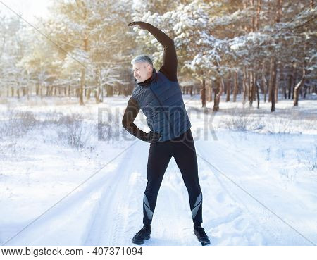 Outdoor Seasonal Sports Concept. Full Length Portrait Of Positive Mature Guy Doing Exercises Before