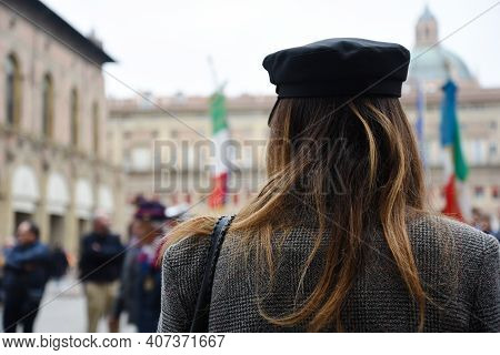 Rear View Of Alternative Woman Wearing Vintage Coat And Sailor Hat Standing In A Square During A Pol
