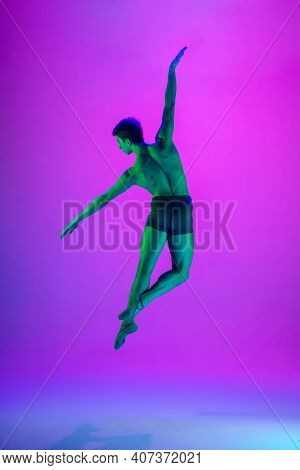 Power. Young And Graceful Ballet Dancer On Purple Studio Background In Neon Light. Art, Motion, Acti