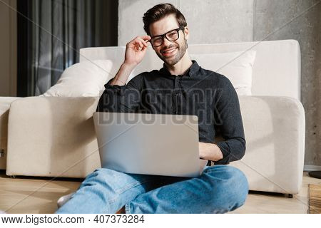 Cheerful unshaven man using laptop while sitting on floor at home