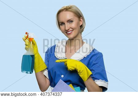 Positive Cleaning Lady Is Pointing At Cleaning Spray. Beautiful Housemaid In Uniform Isolated On Blu