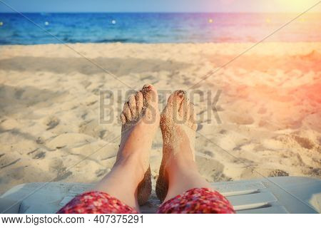 Seascape On The Background Of The Female Foot. A Woman In A Red Dress Near The Water By The Ocean. T