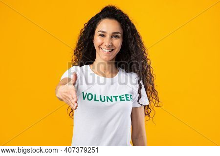 Cheerful Volunteer Woman Offering Hand For Handshake Greeting To Camera Posing Standing Over Yellow