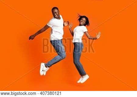 Cute And Cheerful Young Black Couple Jumping Up On Orange Studio Background, Full Length Shot, Copy