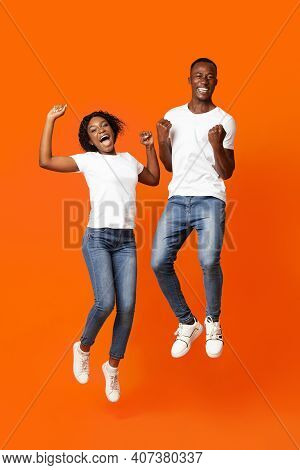 Joyful African American Young Couple Clenching Fists And Screaming, Jumping Up Over Orange Studio Ba