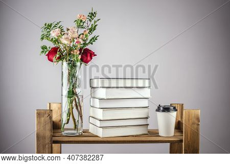 A Vase Of Fresh Beautiful Flowers, A Stack Of Books And A Paper Cup Of Coffee On A Shelf Of A Wooden