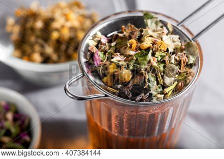 Herbal Tea With Chamomile, Rose And Mint On Gray Background Close-up. Home Remedy Concept