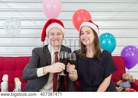 A Man And Woman Wearing A Christmas Hat Hold A Wine Glass To Celebrate Xmas Day.
