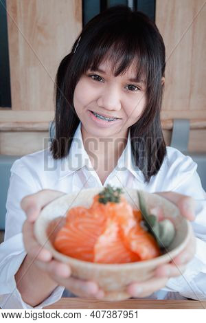 A Girl Teenage Shows A Salmon Don In A Japanese Restaurant.