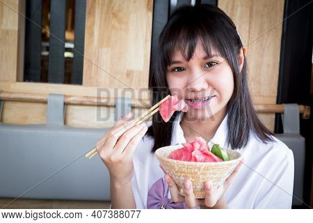 A Girl Teenage Shows A Raw Tuna Uses Chopsticks From Salmon Don In A Japanese Restaurant.