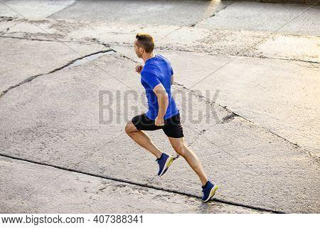Male Runner To Run Morning Jog Along A Concrete Road