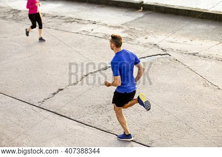 Male And Female Runners Run Towards Each Other. A Morning Jog