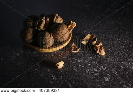 Walnut In Wooden Bowl On Black Background With Copy Space