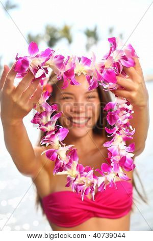 Hawaii woman showing flower lei garland of pink orchids. Beautiful smiling mixed race woman in bikini on beach giving a welcoming Lei on the hawaiian island Big Island.