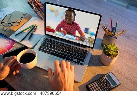 African american schoolgirl learning displayed on laptop screen during video call with male teacher. Online education staying at home in self isolation during quarantine lockdown.
