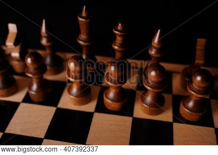 Black Wooden Pieces On A Chessboard. A Chessboard Set Up During A Game On A Black Background