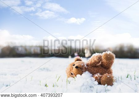 Lost Teddy Bear With Sad Face Lying On Snow With Blurry People,lonely Bear Doll Laying Down On The P