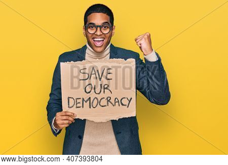 Young handsome hispanic man holding save our democracy protest banner screaming proud, celebrating victory and success very excited with raised arms